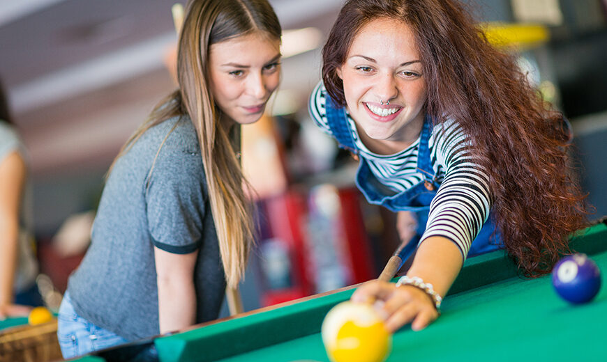 Two girls friends playing pool